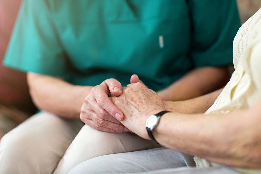 Pflegerin hält Hand einer älteren Dame